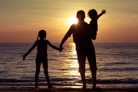 dad and child: Father and children playing on the beach at the sunset time. Concept of friendly family.