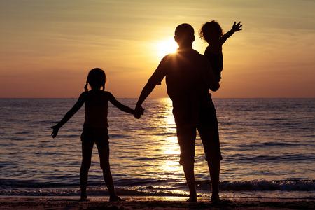 jugando: Padre y ni�os que juegan en la playa de la puesta del sol. Concepto de la familia.