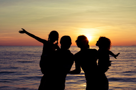 Silhouette of happy family who playing on the beach at the sunset time. Concept of friendly family. photo