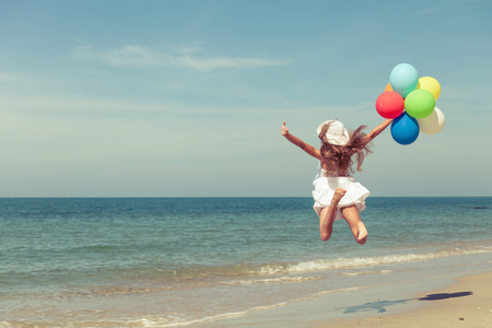 Teen girl with balloons jumping on the beach at the day time 스톡 콘텐츠