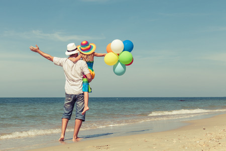 Father and daughter with balloons playing on the beach at the day time. Concept of friendly family. Banco de Imagens
