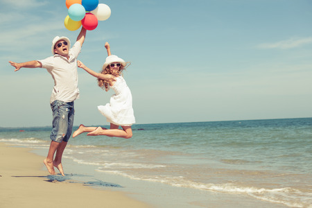 Father and daughter with balloons playing on the beach at the day time. Concept of friendly family. Standard-Bild