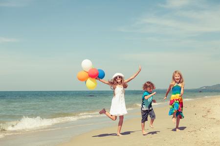 niños bailando: Tres niños felices con globos bailando en la playa en el tiempo del día Foto de archivo