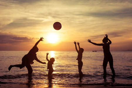 trips: Silhouette of happy family who playing with the ball on the beach at the sunset time. Concept of friendly family.