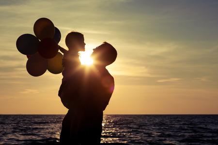 Père et fille avec des ballons jouant sur la plage au coucher du soleil. Concept de la famille. Banque d'images - 35508254