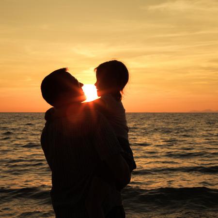 Vater und Tochter spielen am Strand im Sonnenuntergang. Konzept der freundlichen Familie.