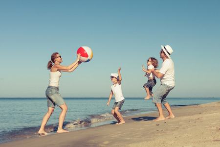 Happy family playing on the beach at the day time.. Concept of friendly family. Stock Photo