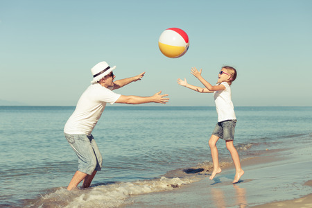 teen beach: Father and daughter playing  with ball on the beach at the day time. Concept of friendly family. Stock Photo