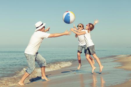 Vader en dochters die op het strand in de dagtijd spelen. Concept van vriendelijke familie.