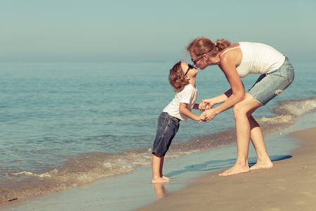 Mother and son playing on the beach at the day time. Concept of friendly family.