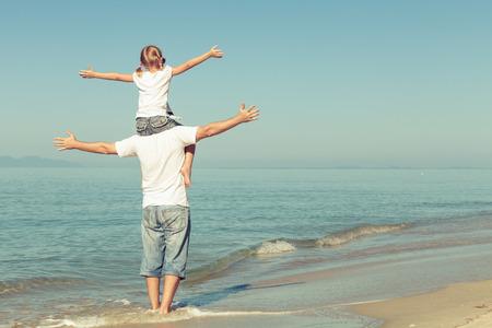 Vater und Tochter spielen am Strand von der Tageszeit. Konzept der freundlichen Familie. Lizenzfreie Bilder