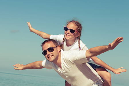 playing in the sea: Father and daughter playing on the beach at the day time. Concept of friendly family. Stock Photo