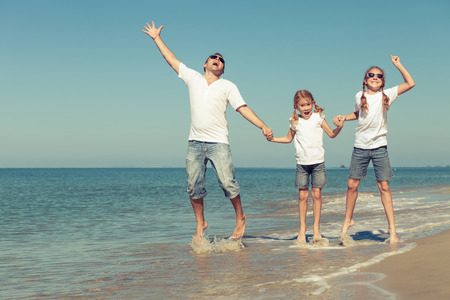 Father and daughters playing on the beach at the day time. Concept of friendly family. photo