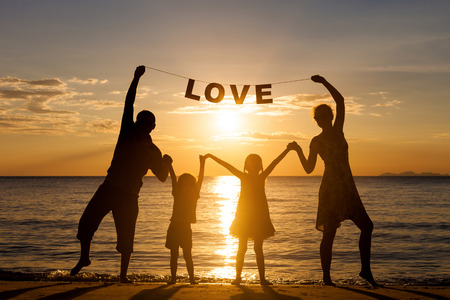 Happy family standing on the beach at the sunset time. Parents hold in the hands  inscription \Love\. Concept of friendly family.