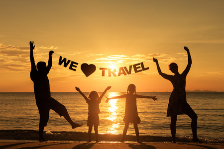 Happy family standing on the beach at the sunset time. Parents hold in the hands  inscription \We love travel\. Concept of friendly family.