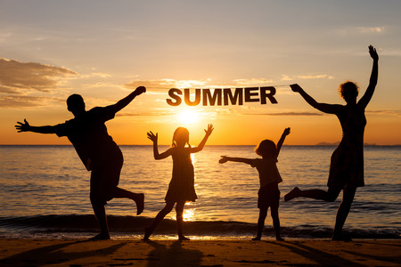 Happy family standing on the beach at the sunset time. Parents hold in the hands  inscription \Summer\. Concept of friendly family. photo