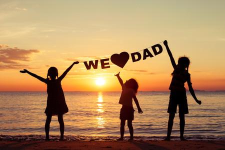 """papa: Enfants heureux de jouer sur la plage au coucher du soleil. Les enfants occupent dans les mains inscription  """"Nous aimons papa """". Concept du jour de p�re heureux."""