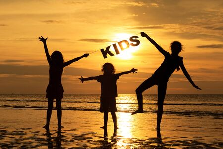 Happy children playing on the beach at the sunset time. Children hold in the hands  inscription \\\Kids\\\ photo