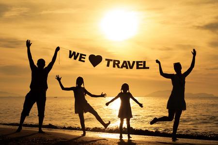 """familia viaje: Familia feliz de pie en la playa de la puesta del sol. Los padres tienen en la inscripci�n de las manos """"Nos encanta viajar"""". Concepto de la familia."""