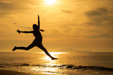 human energy: Happy girl jumping on the beach at the sunset time Stock Photo