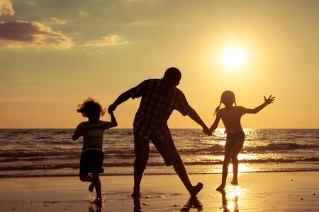donna che balla: Padre e bambini che giocano sulla spiaggia al momento del tramonto. Concetto di familiare. Archivio Fotografico