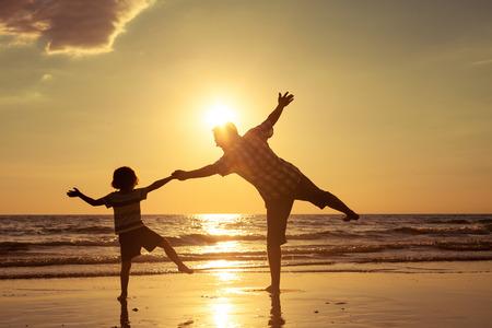 Pai e filho brincando na praia no momento do por do sol. Conceito de fam Banco de Imagens