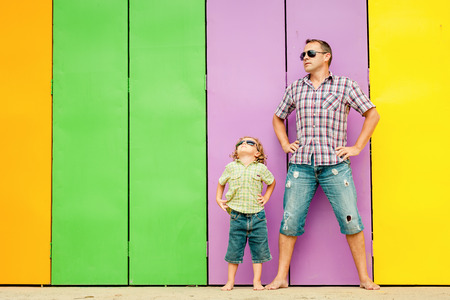 Father and son playing near the house at the day time. They standing near are the colorful wall. Concept of friendly family. Standard-Bild