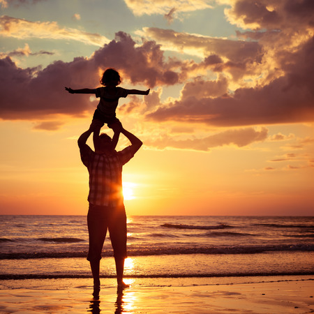 couple having fun: Father and son playing on the beach at the sunset time. Concept of friendly family.