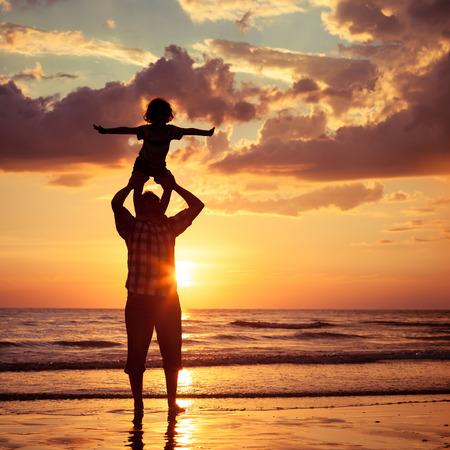 familia viaje: Padre e hijo jugando en la playa de la puesta del sol. Concepto de la familia.