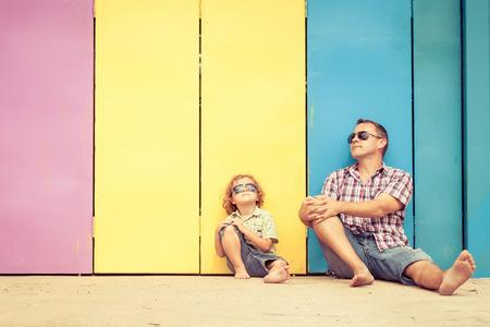Vater und Sohn spielen in der Nähe des Hauses in der Tageszeit. Sie sitzen in der Nähe sind die bunten Wand. Konzept der freundlichen Familie. Standard-Bild - 35851019