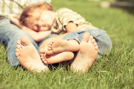 Father and son sitting on the grass at the day time. Concept of friendly family.