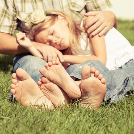 little girl barefoot: Father and daughter sitting on the grass at the day time.  Concept of friendly family.