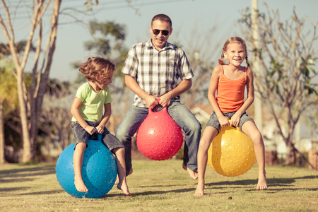 Dad and children playing on the lawn in front of house at the day time Stock Photo