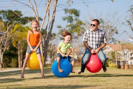 Vader en kinderen spelen op het grasveld voor het huis op de dag de tijd