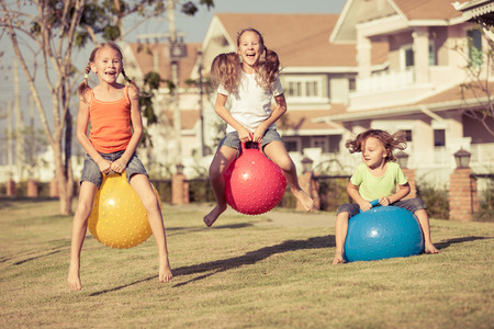 happy kids playing with inflatable balls on the lawn in front of house at the day time