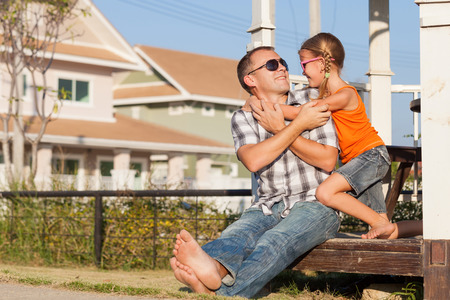 vacation home: Father and daughter playing near the house at the day time. They sit in the white gazebo. Concept of friendly family.