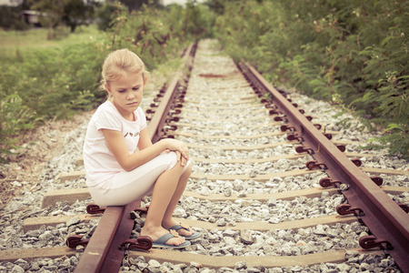 lost child: Portrait of sad blond little girl sitting on the rails at the day time Stock Photo