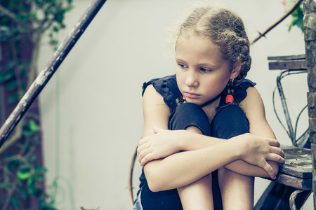 Portrait of sad blond teen girl sitting on the stairs at the day time