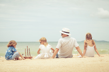 playing in the sea: Father and children playing on the beach at the day time. Concept of friendly family.