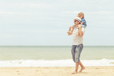 family time: Father and son playing on the beach at the day time. Concept of friendly family.