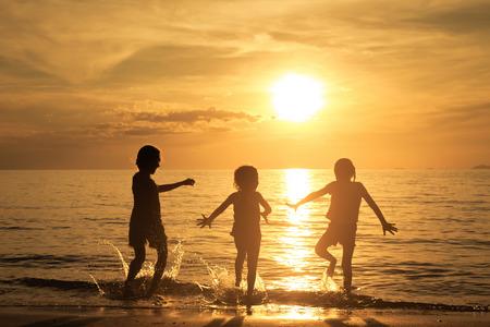 Gelukkige kinderen spelen op het strand bij de zonsondergang tijd Stockfoto