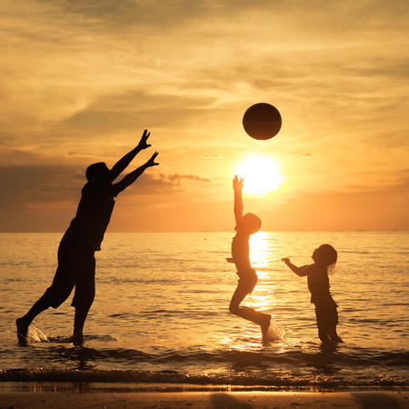 Father and children playing on the beach at the sunset time. Concept of friendly family. photo