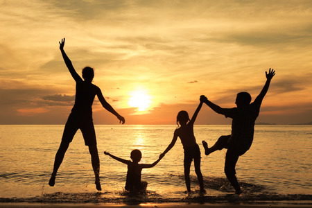 Silhouette of happy family who playing on the beach at the sunset time. Concept of friendly family. Stock Photo