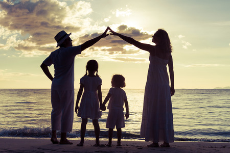 Silhouette of happy family who playing on the beach at the sunset time. Concept of friendly family. Banque d'images