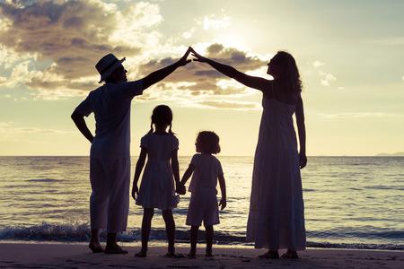 Silhouette der glückliche Familie, die auf dem Strand am Sonnenuntergang spielen. Konzept der freundlichen Familie.