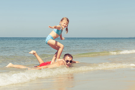 padre e hija: Padre e hija jugando en la playa en el d�a. Concepto de la familia.