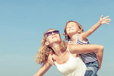 Mutter und Sohn spielen am Strand an der Tageszeit. Konzept der freundlichen Familie.