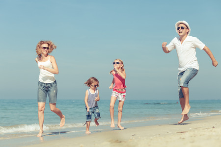 family time: Happy family walking on the beach at the day time. Concept of friendly family.