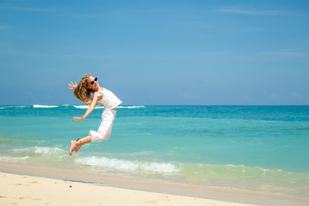 teen girl  jumping on the beach at blue sea shore in summer vacation at the day time photo
