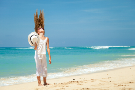 teen girl  standing on the beach at blue sea shore in summer vacation at the day time photo